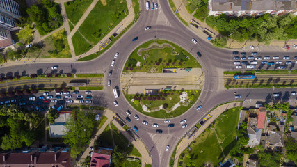 Overhead drone top down shot of busy roundabout with cars and trucks