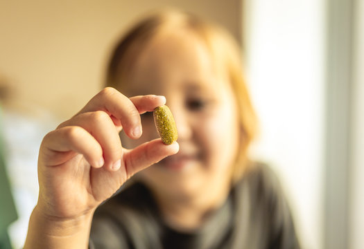 Young boy stares at vitamin or prescription pill that he his holding in hand. Health care or addiction concept.