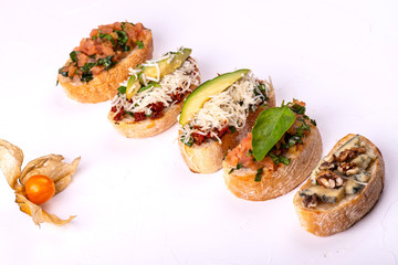 Variety of canape with hummus, tomato, avocado, cheese, walnut and fresh vegetables on white background. Top view of healthy snack concept.