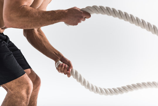 partial view of sportive man doing exercise with ropes on white background