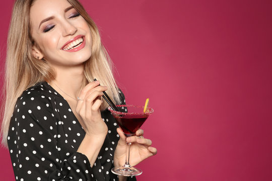 Beautiful young woman with glass of martini cocktail on color background, space for text