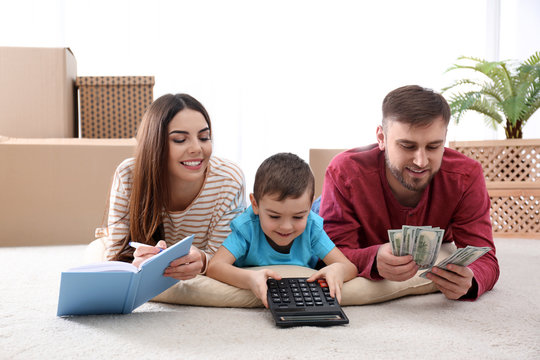 Happy family with money on floor at home