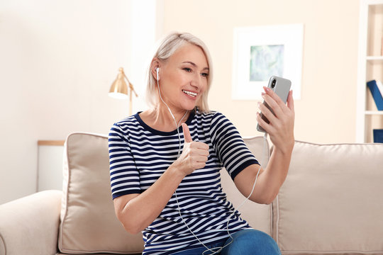 Mature woman using video chat on mobile phone at home