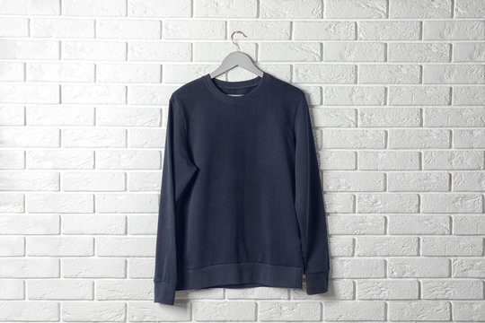 Hanger with dark sweatshirt against brick wall. Mockup for design