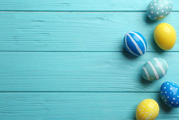 Fotobehang - Flat lay composition of painted Easter eggs on wooden table, space for text