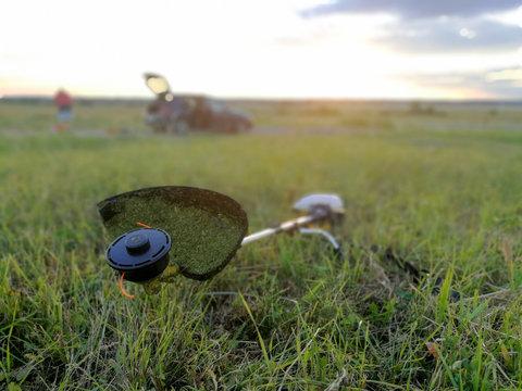 Gasoline grass trimmer on mown grass