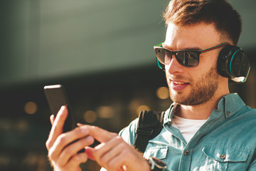 Young man listening to music via headphones and smartphone on the street