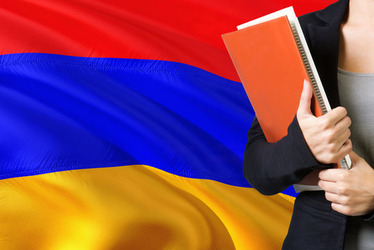 Learning Armenian language concept. Young woman standing with the Armenia flag in the background. Teacher holding books, orange blank book cover.