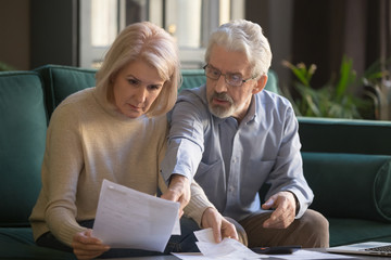 Serious grey haired mature couple calculating bills, checking finances together