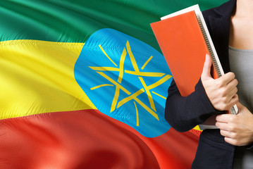 Learning Ethiopian language concept. Young woman standing with the Ethiopia flag in the background. Teacher holding books, orange blank book cover.