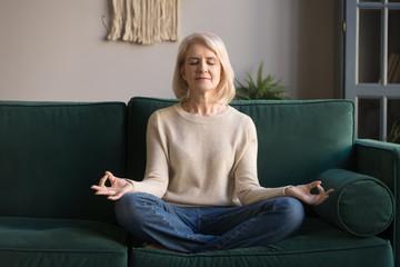 Grey haired mature woman meditating, practicing yoga at home