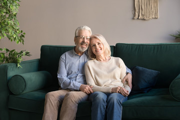 Portrait of hugging aged man and woman, family sitting on couch