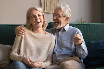 Portrait of middle aged laughing man and woman at home