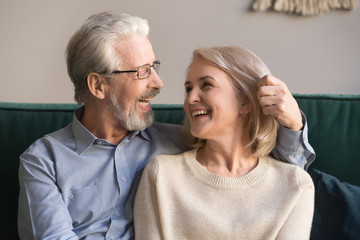 Smiling loving middle aged man and woman enjoying romantic moment
