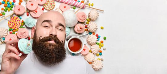 Happy bearded man biting cream cake isolated on white background
