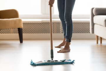 Closeup image barefoot girl doing house cleaning using wet mop