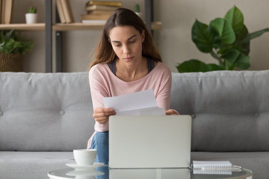 Serious woman sitting on couch reading letter feels frustrated