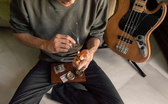 Man sitting on the floor smokes a marijuana joint at home after playing the bass. Rolling a joint. Grinder, paper and weed on a book.