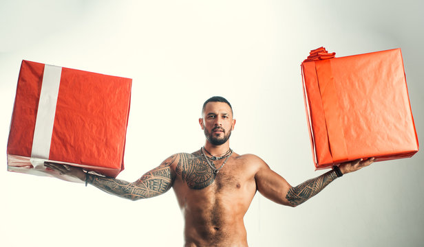 Providing fast gift delivery. Brutal latino man holding gift boxes in strong hands. Bearded hispanic man with wrapped gift boxes. Muscular shirtless guy holiday gifts in red wrap