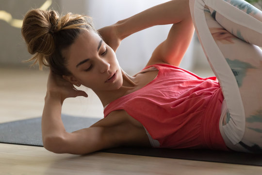 Young attractive woman doing crisscross crunches fitness exercise