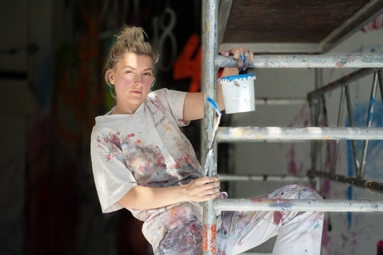 young pretty woman painter climbs on a mobile scaffolding with paint bucket and brush in her hands.