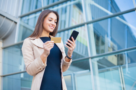 Woman shopping with credit card. Beautiful young lady with gold card using phone