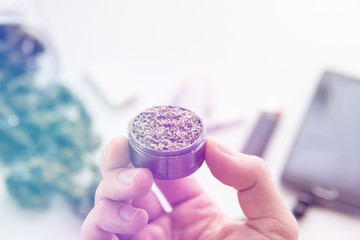 grinder with fresh weed in hand, joint with marijuana, Cannabis buds on white table, close up light leaks color tones