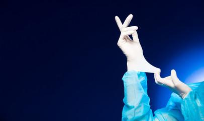 Doctor Nurse woman hand in uniform with Hygiene cap, glasses wearing white glove elastic fingers in Medical hospital, portrait, studio lighting gradient blue background copy space