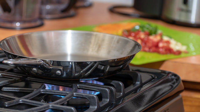 Stainless steel frying pan on lit modern gas stove in preparation for cooking food. Chopped ingredients for meal blurred in background on green chopping/cutting board on counter top.
