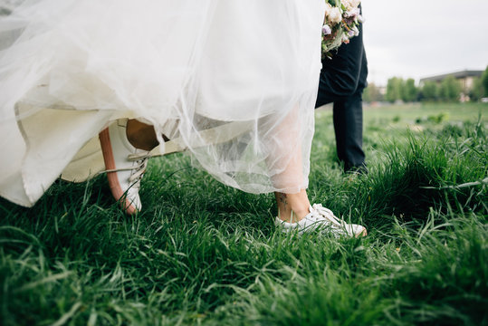the bride and groom are funny and happy step on the grass