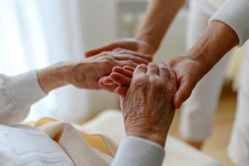 Rentnerin wird bei den Händen gehalten, Fürsorge im Alter