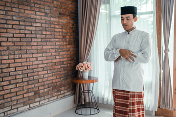 asian muslim man solat or praying by himself at home
