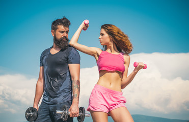 Building up muscle. Couple of athletes doing muscle training with dumbbells. Fit woman and strong bearded man developing muscle tissue. Sexy woman and hipster doing muscle strengthening exercises