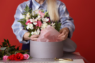 Florist with beautiful bouquet and gift box at table, closeup