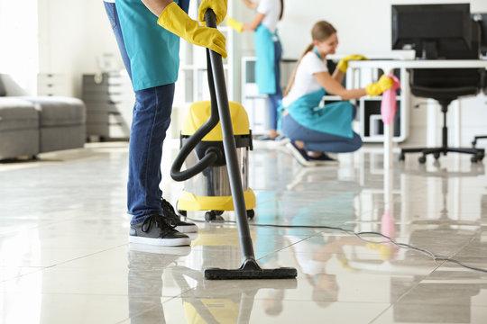 Janitor hoovering floor in office