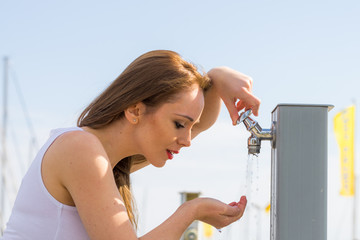 Woman drinking water from street tap