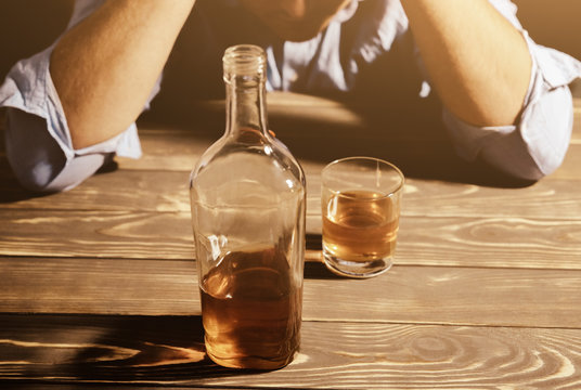 Alcoholic addict. Man near the table with alcohol and a glass. Dangerous habit. Unhealthy life concept. Social problem.