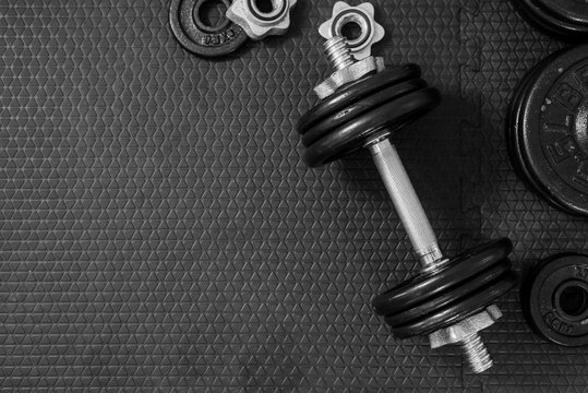 Top view of Iron dumbbells or weights on black floor with copy space for text. Flat lay composition. Health care concept.