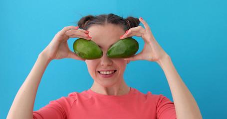 Cheerful Woman Making Avocado Eyes blue background