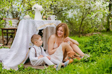 young mother son sit together playing relaxing under tablecloth table form of hut in blooming garden spring flowers during summer holidays.