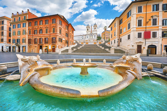 Rome, Italy. Fountain of the Boat (Fontana della Barcaccia) on Spanish square (Piazza di Spagna) at the bottom of Spanish stairs famous landmark design by Bernini. Summer day and blue sky with clouds.