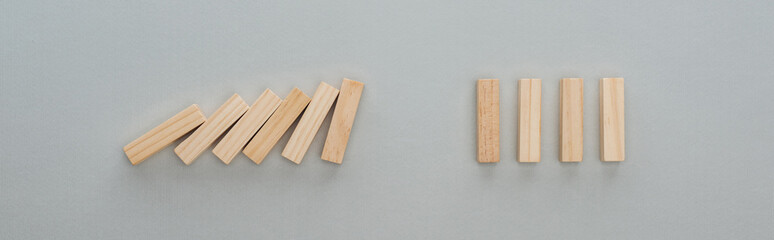 panoramic shot of of falling wooden blocks isolated on grey, domino effect concept Wall mural