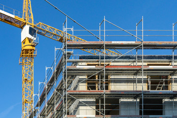 building under construction - construction site with scaffolding at the outside