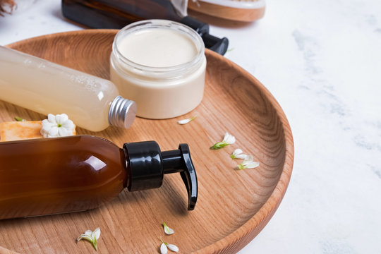 Natural cosmetics in small bottles on the white marble table