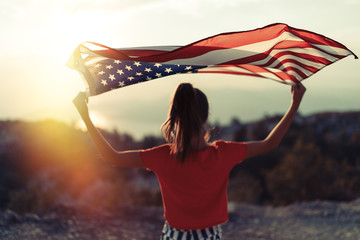 Child girl is waving American flag on top of mountain at sky background. Sunset time
