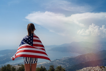 Child teenager girl on the top of the mountain with an American USA flag on her shoulders