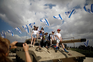 A woman takes a photo of teens as they stand atop of an old tank during Memorial Day ceremony at Latrun's armoured corps memorial site, Israel