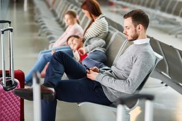 Familie mit zwei Kindern wartet in der Flughafen Ruhezone