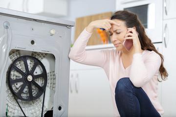 woman is calling a plumber to repair the leak
