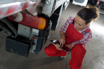 female truck mechanic using tablet pc
